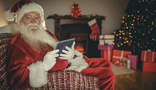 Cheerful santa using tablet on the couch at home in the living room